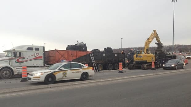 Crews used a back-hoe to remove a leaking transformer from a flatbed truck on Thursday.