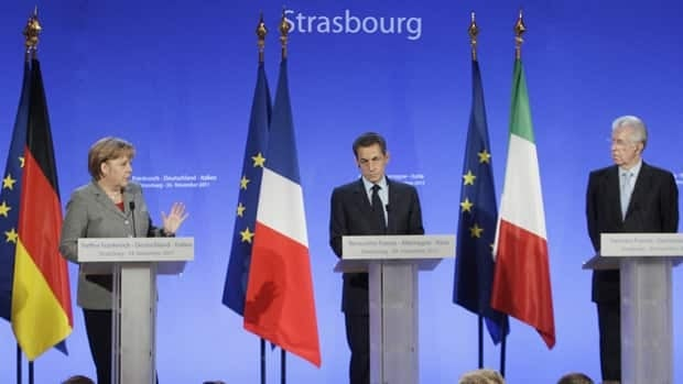 German Chancellor Angela Merkel, left, gestures during a joint press conference with France's President Nicolas Sarkozy, center, and Italy's Prime Minister Mario Monti, in Strasbourg, eastern France, Thursday, Nov 24, 2011. The German leader said her country may be open to expanding the economic bloc's bailout fund.