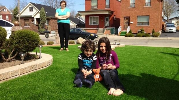 Maria Couto keeps an eye on grandchildren Nicolas and Kayla. When people ask how she got such a nice lawn, she tells them, I bought it.
