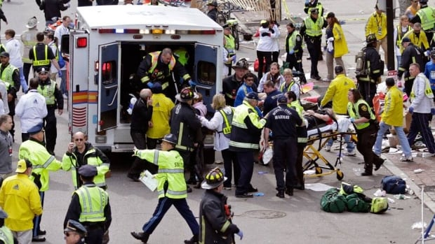 Medical workers aid injured people at the finish line of the 2013 Boston Marathon on Monday after two bombs exploded.