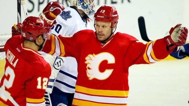 Toronto Maple Leafs' goalie Jonas Gustavsson skates away from celebrating Calgary Flames' Jarome Iginla, left, and Olli Jokinen during third period NHL hockey action in Calgary, Alta.  The Calgary Flames beat the Toronto Maple Leafs 5-1.