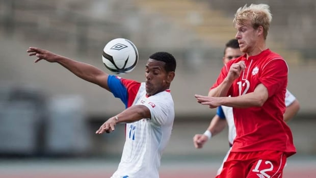 Canada's Kyle Bekker (12) battles against the Costa Rica's Kenny Cunningham, left, during the first half of a soccer friendly Edmonton Tuesday night.
