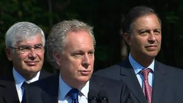 Liberal Leader Jean Charest, centre, is fighting to hold on to his party's eight seats in the Quebec City area, including the riding held by Economic Development Minister Sam Hamad, right.