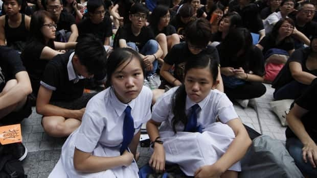 Students held a sit-in protest outside government headquarters in Hong Kong Friday against the government's plan to introduce a new subject Moral and National Education into a new curriculum.