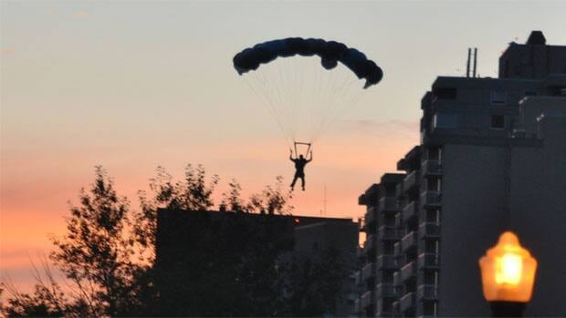 One of three base jumpers fly over the Edmonton skyline Sunday night.