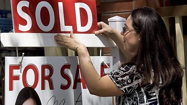 A real estate agent puts up a sold sign in front of a house in Toronto. Some experts have warned Canada's housing market is overheated.