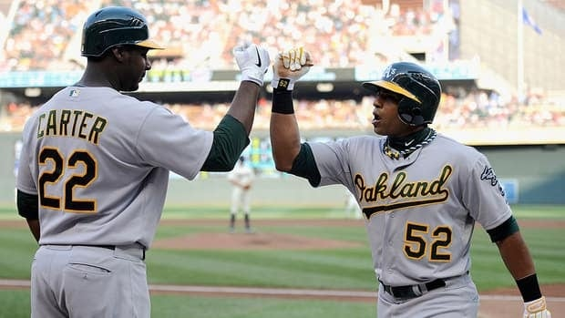 Yoenis Cespedes, right, is among a number of young players leading the Oakland Athletics up the AL West standings.