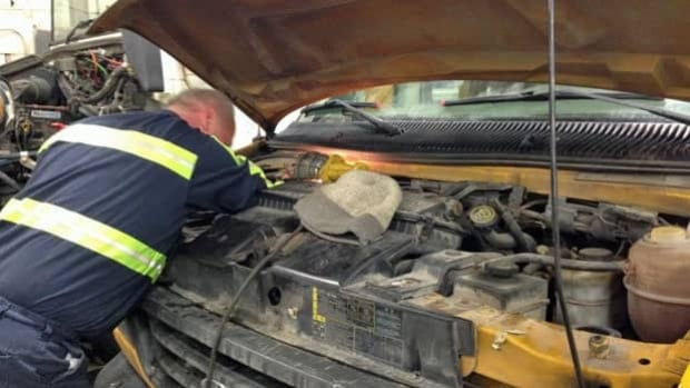 A mechanic works on a school bus in a Sudbury repair shop.