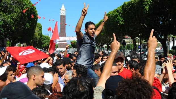 Protesters gather on the main avenue of Tunis after the leader of a leftist Tunisian opposition party, Mohammed Brahmi, was gunned down as he left home.