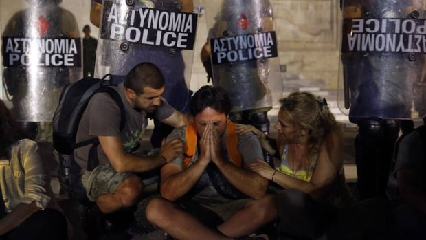 One of 2,000 municipal public school guards to lose their jobs in Greece is comforted by colleagues in front of the parliament in Athens, after the government narrowly approved new austerity measures.