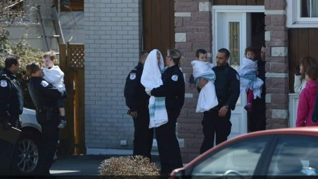 Parents pick up children from the care of police at the scene of the shooting at a daycare in Gatineau on Friday.