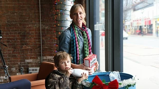Sharlene Louden, owner of Kinder Kinetics, a fitness company, and Quinn donate items on behalf of her clients to CBC Hamilton's Sounds of the Season food drive on Dec. 19. (Cory Ruf/CBC)