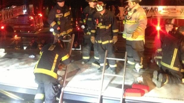 Boston Fire Department firefighters rescue those trapped inside a bus after it struck a bridge in Boston.