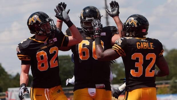 Hamilton Tiger-Cats running back C.J. Gable, right, celebrates his touchdown with teammates Greg Ellingson, left, and Joel Figueroa in Guelph, Ont., Saturday.