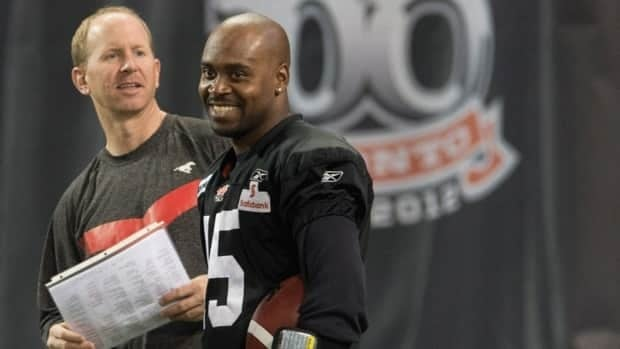 Calgary Stampeders quarterback Kevin Glenn and coach Dave Dickenson share a laugh during a practice Thursday, November 22, 2012 in Toronto. The Stampeders will face the Toronto Argonauts in the 100th CFL Grey Cup Sunday.