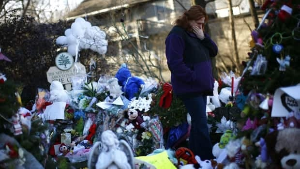 A woman stands at a makeshift memorial for victims of a December 14 shooting at Sandy Hook Elementary school in Newtown, Conn., on Thursday.