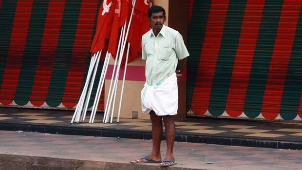 A man stands in front of a closed restaurant as he waits for the start of a protest march in the southern Indian city of Kochi Tuesday. Hundreds of thousands of workers from several trade unions went on strike across India on Tuesday to express their anger at soaring prices and to back demands for improved rights for employees, trade unions said.