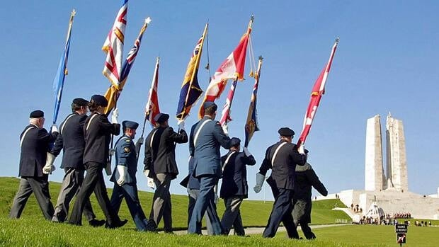 Second World War veterans carry Canadian flags, right, and the United Kingdom's flag, centre, as they march towards the Vimy War Memorial in northern France on April 7, 2002, as part of a ceremony marking the 85th anniversary of the battle of Vimy Ridge.