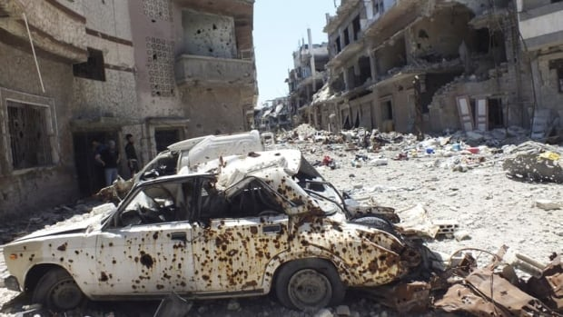 A destroyed car on a street in the besieged area of Homs. Russia says it will continue weapons sales to the Syrian regime even as it presses for a peaceful solution to the two-year old civil war.