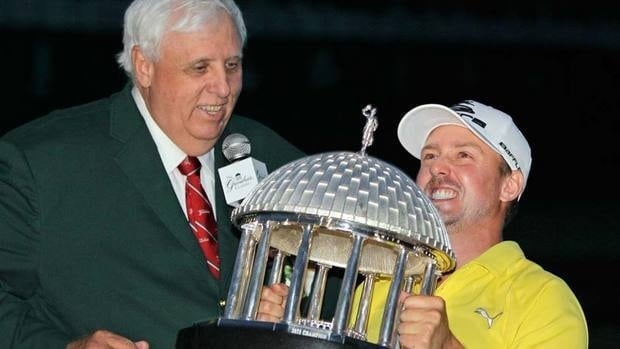 Jonas Blixt struggles to lift the trophy as Greenbrier resort owner Jim Justice, left, watches after Blixt won the Greenbrier Classic PGA golf tournament on Sunday.