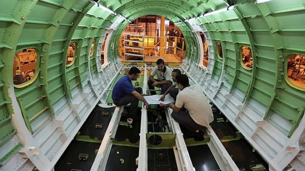Employees work on the fuselage of an Embraer jet in Brazil. The economies of developing world nations, such as Brazil, will soon make up half of the world's GDP.