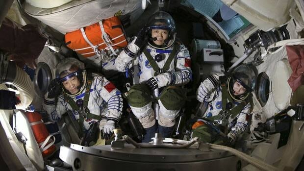 Chinese astronauts Zhang Xiaoguang, Nie Haisheng and Wang Yaping salute in a re-entry capsule during a training at Beijing Aerospace City in Beijing, April 29, 2013.