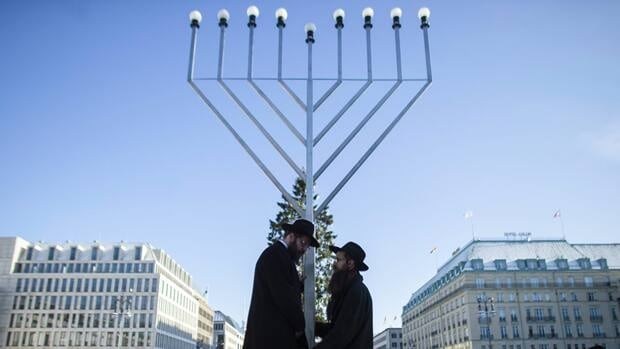 Rabbi Yehuda Teichtal, centre left, and Rabbi Segal Shmoel install a giant Hanukkah menorah near the Brandeburg Gate in Berlin on Friday. The eight-day Jewish festival of lights Hanukkah starts on Dec. 8.