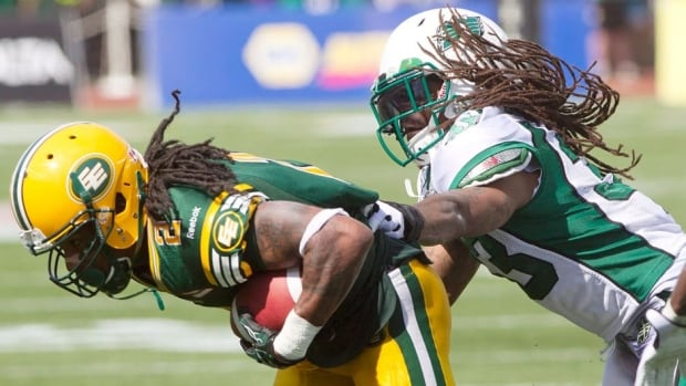 Saskatchewan Roughriders' Dwight Anderson, right, tackles Edmonton Eskimos Fred Stamps during the second half action in Edmonton on Saturday.