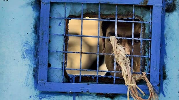 A prisoner looks out of his cell window at the main prison in Kandahar, Afghanistan in this April 2011 file photo. A new United Nations report says Afghan authorities are still torturing prisoners.