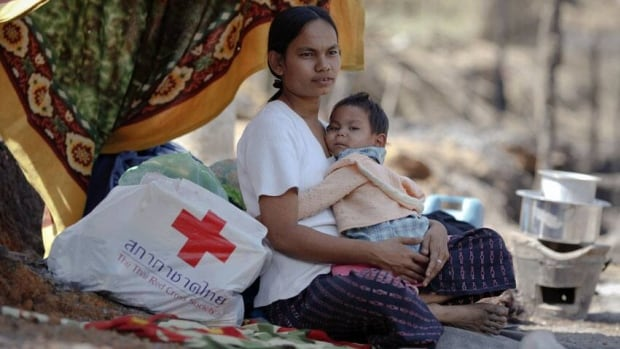 A refugee woman from Burma holds her child after receiving some aid at a refugee camp along the Thai-Burma border. Red Cross officials have said they will resume visits to prisons in Burma, also known as Myanmar, seven years after a military junta.