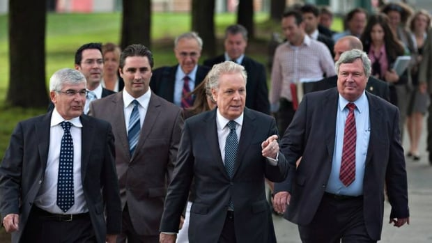 Jean Charest, who announced his resignation as Quebec Liberal leader on Wednesday, leads a number of his MNAs and candidates to a news conference last month during the election campaign. No one has yet jumped at the chance to replace him.