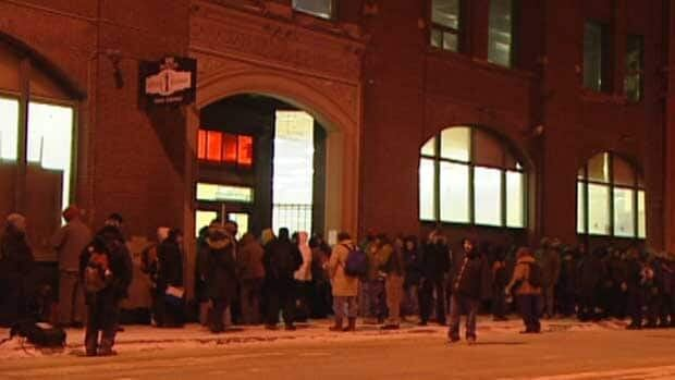 People line up outside Siloam Mission in downtown Winnipeg on Thursday night.