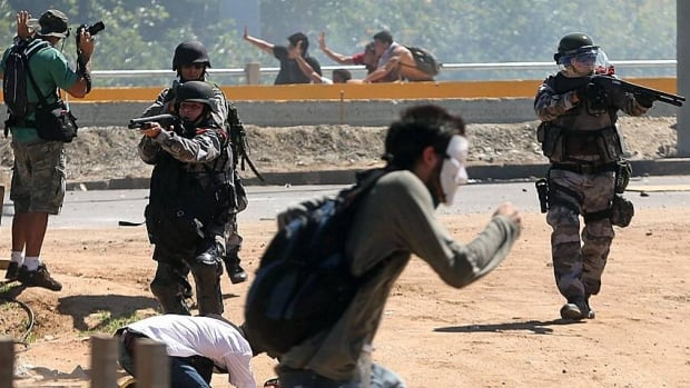 Riot police aim their weapons at protesters gathering near Castelao stadium in Fortaleza, Brazil, on Wednesday. Protesters cut off the main access road to the stadium ahead of the Brazil-Mexico match in the Confederations Cup soccer tournament.