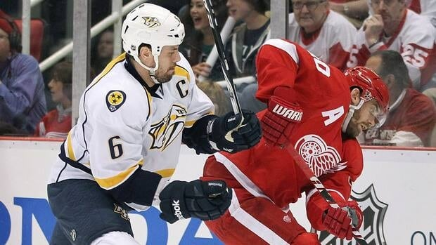 Predators defenceman Shea Weber, left, tries to check Red Wings centre Henrik Zetterberg during the first period of Game 3 on Sunday.