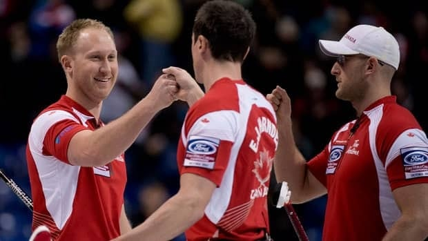 Canada skip Brad Jacobs, left, celebrates his team's win over Denmark with E.J. Harnden, centre, and Ryan Harnden following a page 3-4 playoff draw at the World Men's Curling Championship in Victoria, B.C., on Saturday.