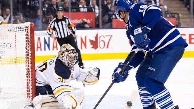 Toronto Maple Leafs forward Joffrey Lupul, right, gets poke checked by Buffalo Sabres goalie Ryan Miller, left, in Toronto on Monday, Jan. 21, 2013.