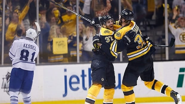 Patrice Bergeron and Zdeno Chara of the Boston Bruins celebrate their winning overtime goal as Phil Kessel of Toronto skates away.