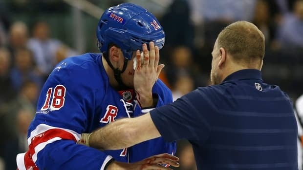 Marc Staal of the New York Rangers is helped off the ice after he was hit in the face with a puck in the third period against the Philadelphia Flyers on March 5, 2013.