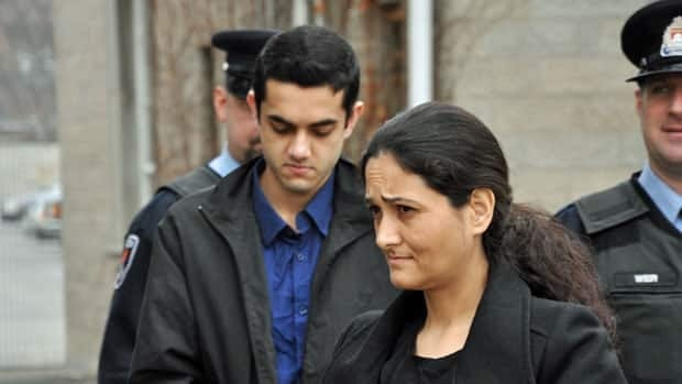 Tooba Yahya, centre, and her son Hamed Shafia are escorted to the courtroom at the Frontenac County Courthouse in Kingston, Ont., on Wednesday.