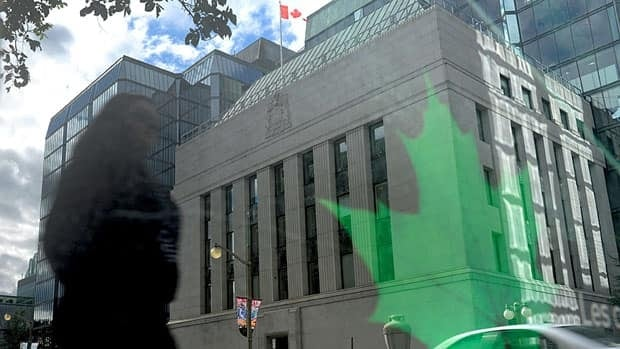 The Bank of Canada is reflected in signage on a bus stop in Ottawa in September. The Bank warns that Europe's deteriorating debt crisis poses risks to Canadians with large debts.