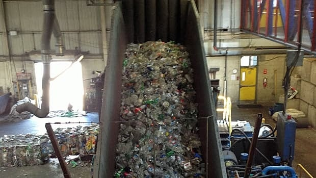 Thousands of plastic bottles make their way up a conveyor belt at the Region of Waterloo landfill. The region is losing millions of dollars from depressed commodity prices for recycled goods and stiff competition from private sector haulers.