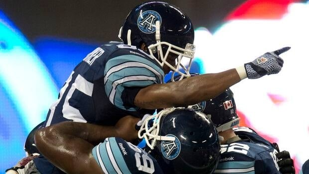 Toronto Argonauts wide receiver Sammie Parker, left, is hoisted aloft by teammates Stephen Good, right, and Darion Smith after scoring the game winning touchdown in fourth quarter CFL pre-season action against the Montreal Alouettes in Toronto on Tuesday June 19, 2012.