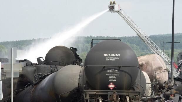 Fire fighters keep watering railway cars the day after a train derailed causing explosions of railway cars carrying crude oil Sunday, July 7, 2013, in Lac-Mégantic, Que. The NDP is proposing the House of Commons transport committee reconvene this summer to discuss rail safety.