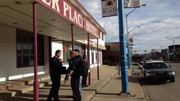 Police speak with people outside the Jasper Place Hotel after an alleged robbery Saturday afternoon.