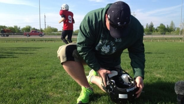 Brian Guebert, from Saskatoon Minor Football, inserts a concussion sensor into a helmet.