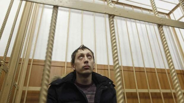 Pavel Dmitrichenko looks out from the defendant's holding cell during a court hearing in Moscow on Thursday. Dmitrichenko, a Bolshoi Ballet dancer accused of organising an attack that nearly blinded the Russian theatre's artistic director, said in court that he did not intend for the victim to be splashed with acid.
