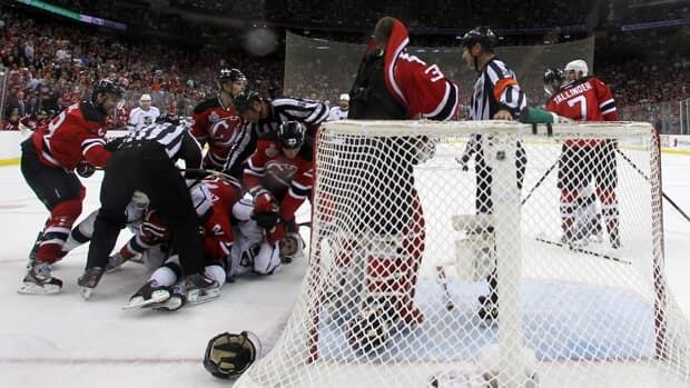 Martin Brodeur (30) of the New Jersey Devils has his jersey pulled over his face as Devils and Los Angeles Kings players shove each other in the third period during Game Five on Saturday in Newark, New Jersey.