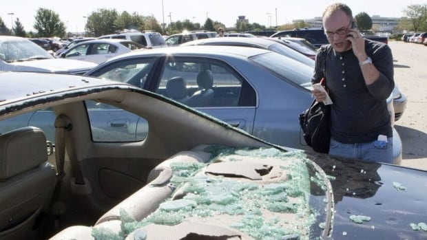 A man calls his insurance company after a thunderstorm damaged his car. Ontario has pledged auto insurance rates will decline by 8 per cent in the coming year.