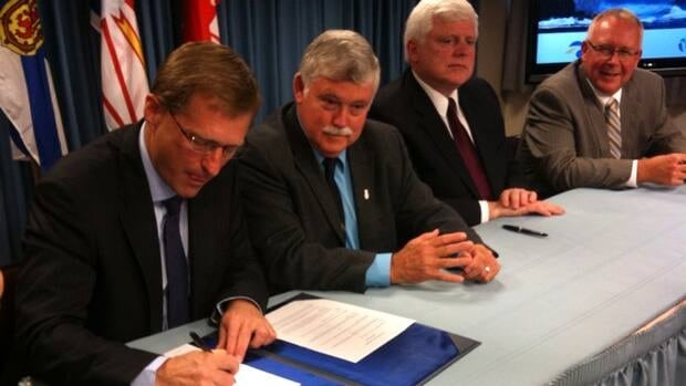 Newfoundland and Labrador Natural Resources Minister Jerome Kennedy signs a Muskrat Falls  legal agreement during a ceremony Tuesday in St. John's, accompanied by Nova Scotia counterpart Charlie Parker, Nalcor CEO Ed Martin and Emera CEO Chris Huskilson.