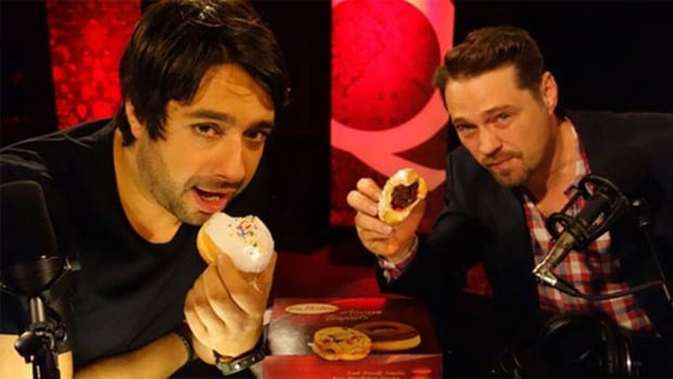Jason Priestley, right, eats 'The Priestley' doughnut with CBC Q host Jian Ghomeshi during an April interview.